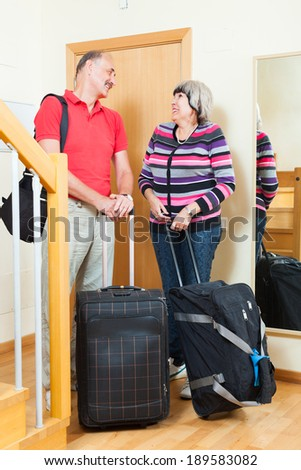 Happy mature couple with luggage   near door going on holiday