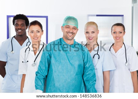 Happy Mature Doctor In Surgical Gown With His Coworkers