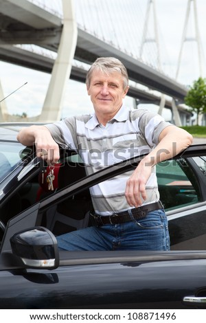 Happy mature driver with ignition key standing near the car - stock photo