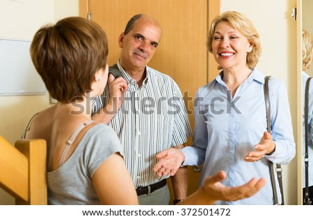 Happy mature family couple visiting daughter at home - stock photo