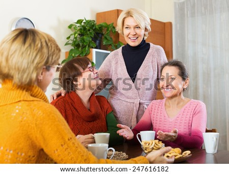 Happy mature female having cup of hot tea indoor and smiling - stock photo