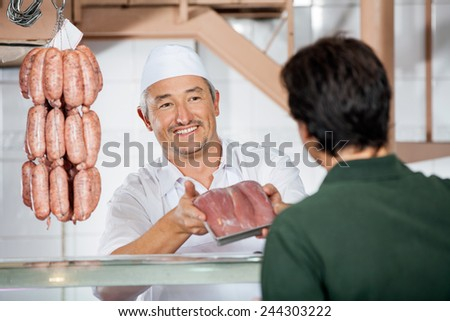 Happy mature male butcher showing packed sausages to customer at butchery - stock photo