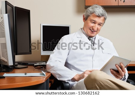 Happy mature male doctor holding digital tablet while sitting by desk in clinic