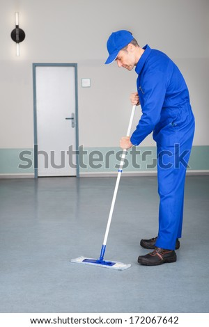 Happy Mature Male Worker Cleaning Floor With Mop - stock photo