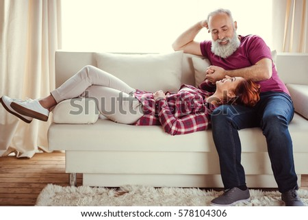 Happy mature man looking at beautiful smiling woman lying on sofa