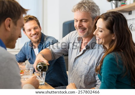 Happy mature man pouring wine into glass 