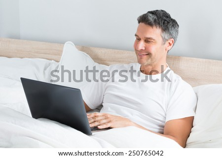 Happy Mature Man Sitting On Bed Using Laptop