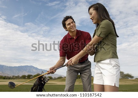 Happy mature man teaching woman to play golf - stock photo