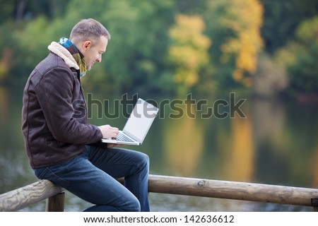 Happy mature man using laptop while sitting on fence against lake - stock photo