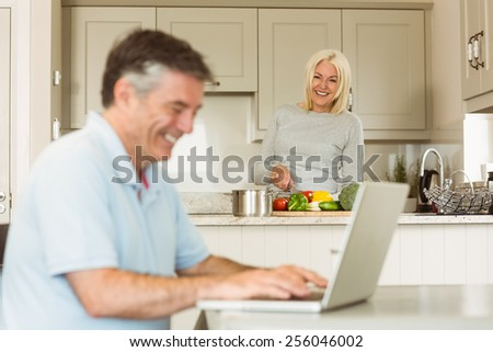 Happy mature man using laptop while wife prepares vegetables at home in the kitchen - stock photo