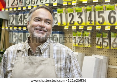 Happy mature salesperson in hardware store looking away - stock photo