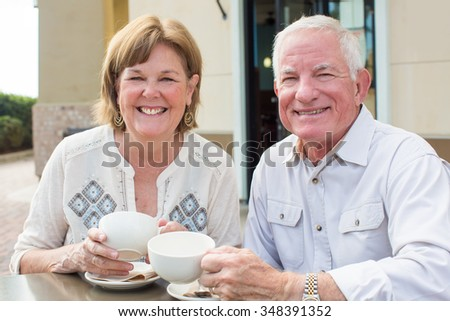 Happy mature senior couple reading a newspaper outside at a cafe - stock photo