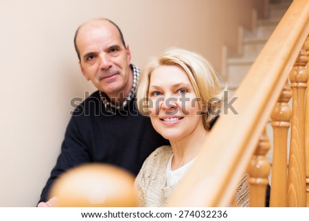 Happy mature spouses leaning against stairway indoor