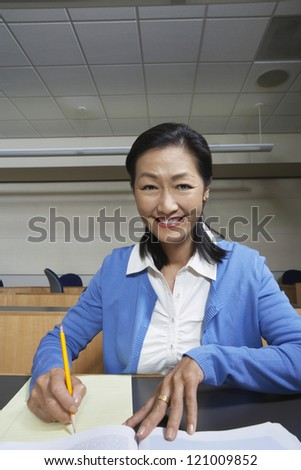 Happy mature teacher writing notes in classroom