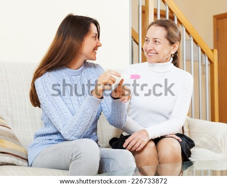 Happy mature woman and adult daughter with pregnancy test at home interior