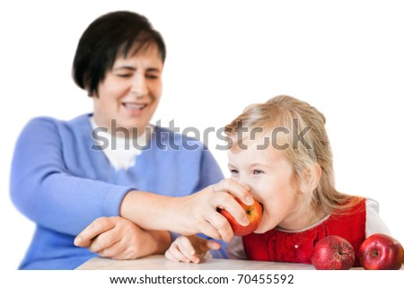 happy mature woman and little girl with apples isolated on white background