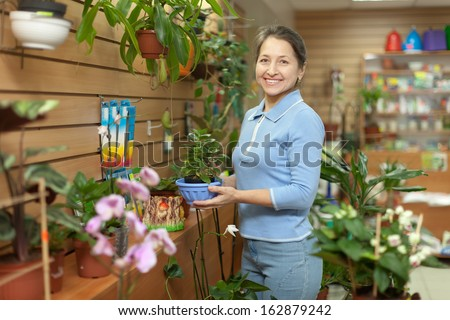 Happy mature woman chooses Kalanchoe plant at flower shop