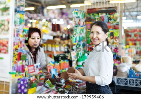 Happy mature woman chooses solid fertilizer at market. Consultant helps her