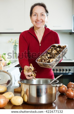 Happy mature woman cooking lent diet soup with dried mushrooms - stock photo