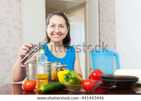 Happy mature woman cooking lunch with vegetables at her kitchen   - stock photo