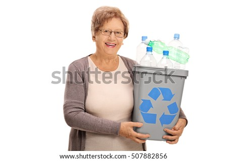 Happy mature woman holding a recycling bin full of plastic bottles isolated on white background