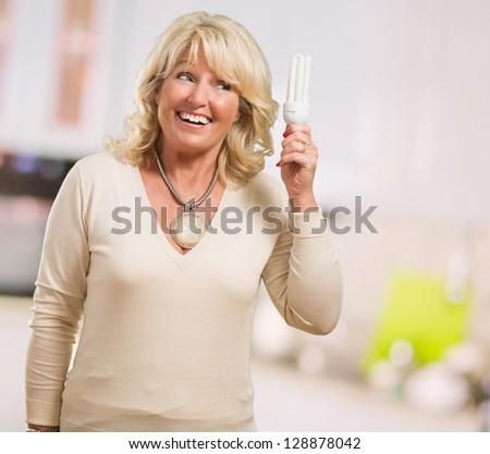 Happy Mature Woman Holding Bulb Light, indoor - stock photo