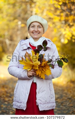 Happy mature woman  in jacket outdoors in autumn