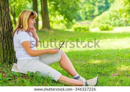Happy mature woman in the park with a laptop - stock photo