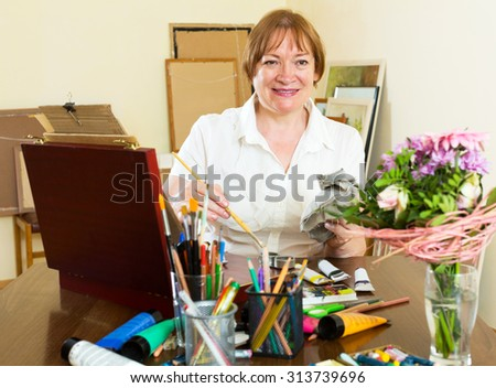 Happy mature woman painting a new picture - stock photo
