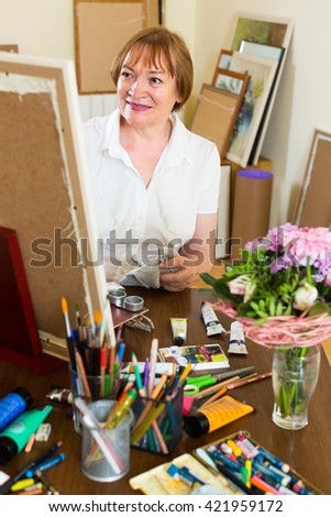 Happy mature woman painting for fun with paints at home studio - stock photo