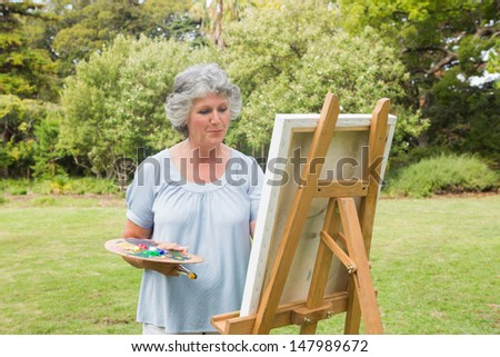 Happy mature woman painting on canvas in park
