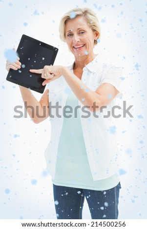 Happy mature woman pointing to tablet pc against snow falling - stock photo