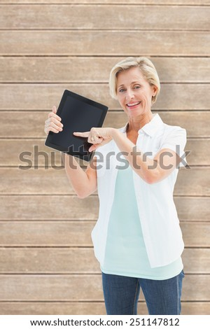 Happy mature woman pointing to tablet pc against wooden planks - stock photo