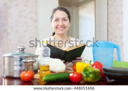 Happy mature  woman reads cookbook for recipe at kitchen