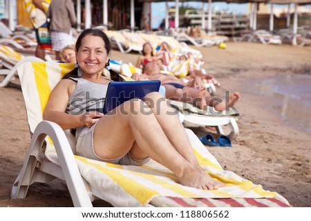 Happy mature woman sitting  with laptop at resort beach
