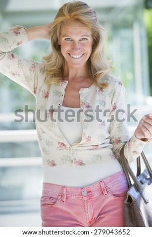Happy mature woman smiling outdoors with purse - stock photo