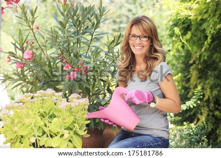 Happy mature woman taking care of her plants ( and watering them ) in her garden.