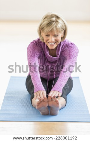Happy mature woman touching toes while sitting on yoga mat at home - stock photo