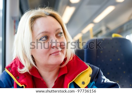 Happy mature woman travelling in a train