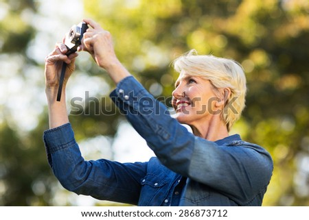 happy mature woman using a camera to take photo outdoors at the park - stock photo