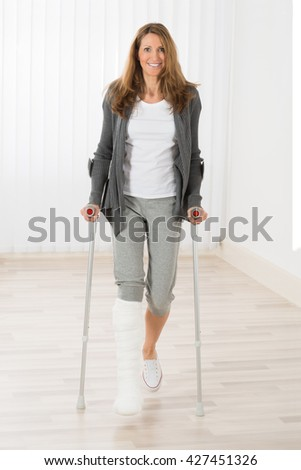 Happy Mature Woman With Fractured Leg Holding Crutches While Walking - stock photo