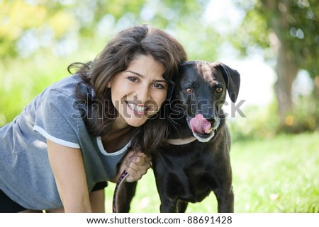 Happy mature woman with her black labrador retriever dog in the yard - stock photo