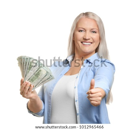 Happy mature woman with money showing thumb-up gesture on white background