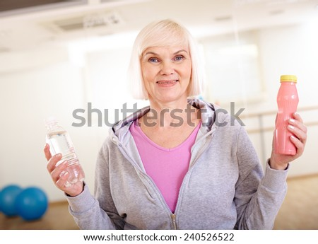 Happy mature woman with plastic bottles of water and yoghurt looking at camera - stock photo