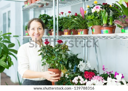 Happy mature woman with roses plant in flower store - stock photo
