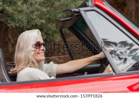Happy mature woman with sunglasses driving red convertible on sunny day