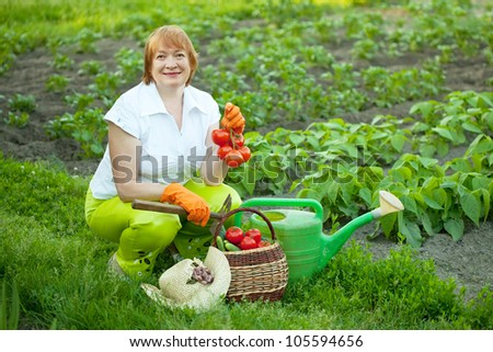 Happy mature woman with vegetables harvest