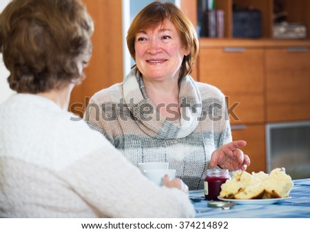 Happy mature women sitting at table and chatting - stock photo