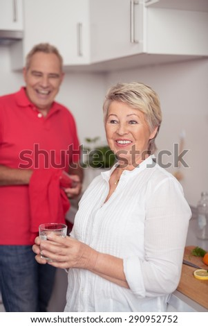 Happy Matured Wife Having a Glass of Water After Preparing Something at the Kitchen with his Husband. - stock photo