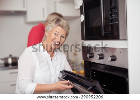 Happy Matured Woman Opening a Microwave Oven at the Kitchen While Looking at the Camera with a Toothy Smile. - stock photo
